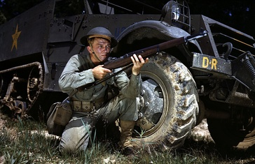 Infantryman wearing a Brodie helmet, kneeling in front of M3 Half-track, holds an M1 Garand rifle. Fort Knox, June 1942.