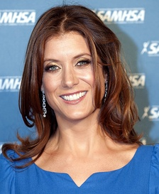Kate Walsh smiling at the camera in a blue dress