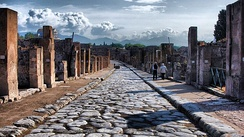 Stone curbs and raised sidewalks on both sides of a 2000-year-old paved road in Pompeii, Italy