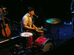 The band members play multiple instruments in live performances. Here Marcus Mumford sits at a drum kit.