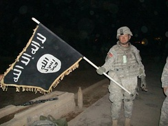 U.S. Army soldier with captured ISIL flag in Iraq, December 2010