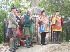 The Honourable Adam Bruce (far right) at his installation as Finlaggan Pursuivant of Arms of Clan Donald. Finlaggan wears a tabard emblazoned with the arms of his employer, the Chief of Clan Donald.