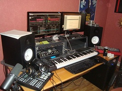 A typical home studio setup for EDM production with computer, audio interface and various MIDI instruments.