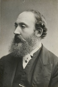 George Butler in profile, wearing a suit; his hair is receding and he has a large beard
