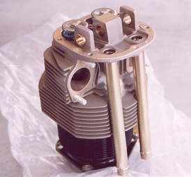 A cylinder from an air-cooled aviation engine, a Continental C85. Notice the rows of fins on both the steel cylinder barrel and the aluminum cylinder head. The fins provide additional surface area for air to pass over the cylinder and absorb heat.