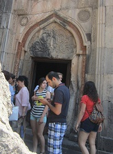 Cultural tourism: tourists outside a Geghard monastery in Armenia, 2015