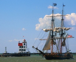 At an Ohio history festival, the 19th-century style brig warship USS Niagara passes the Lorain lighthouse.