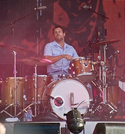 Coghill is playing his drum kit, his right arm is crooked, holding a drumstick and hitting the drum rim situated slightly to his left. His left arm and most of his lower body is obscured by the rest of the kit. He stares off to his right with his lightly bearded chin slightly raised. He is dressed in a pale blue sleeveless shirt and similar coloured pants. In front and above his kit are microphones and band equipment. Behind him is a large graphic design, consisting of red-orange lights and black dots.