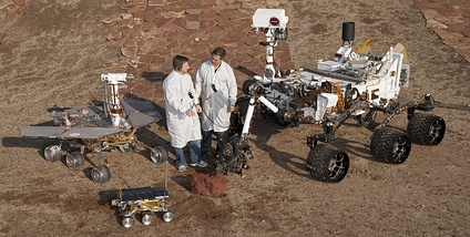 Two Jet Propulsion Laboratory engineers stand with three vehicles, providing a size comparison of three generations of Mars rovers. Front and center is the flight spare for the first Mars rover, Sojourner, which landed on Mars in 1997 as part of the Mars Pathfinder Project. On the left is a Mars Exploration Rover (MER) test vehicle that is a working sibling to Spirit and Opportunity, which landed on Mars in 2004. On the right is a test rover for the Mars Science Laboratory, which landed Curiosity on Mars in 2012. Sojourner is 65 cm (2.13 ft) long. The Mars Exploration Rovers (MER) are 1.6 m (5.2 ft) long. Curiosity on the right is 3 m (9.8 ft) long.