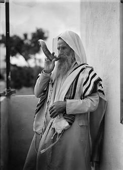 A man in a tallit blows the shofar