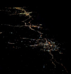 Night aerial view of Stamford from the west, with Norwalk, Bridgeport, and New Haven behind to the northeast.  The dark area in the upper right is the Long Island Sound.