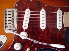 Detail of a Squier-made Fender Stratocaster. Note the vibrato arm, the 3 single-coil pickups, the volume and tone knobs.