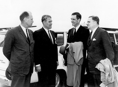 Four men in suits are outdoors, speaking to each other in front of a large white automobile.