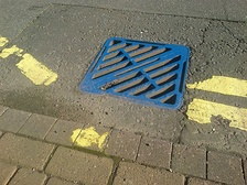 Blue drain and yellow fish symbol used by the UK Environment Agency to raise awareness of the ecological impacts of contaminating surface drainage.