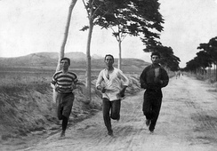 "Burton Holmes's photograph entitled ""1896: Three athletes in training for the marathon at the Olympic Games in Athens"".[18][19]"