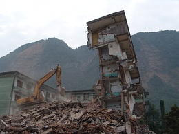 A collapsed structure being bulldozed, with a exposed mountain face in the background