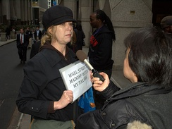 A protester on Wall Street in the wake of the AIG bonus payments controversy is interviewed by news media.