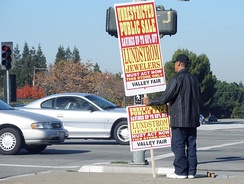 Paying people to hold signs is one of the oldest forms of advertising, as with this human billboard.