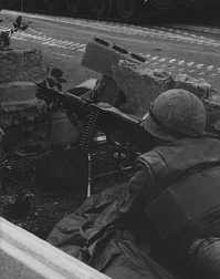 A Marine heavy machine gunner monitors a position along the international neutral corridor in Santo Domingo, 1965.