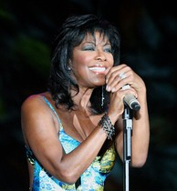 A woman in her late fifties. She wears a blue sleeveless top and is holding a microphone and smiling.