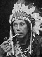 Chief William Neptune of the Passamaquoddy, wearing a headdress and outfit adorned with swastikas