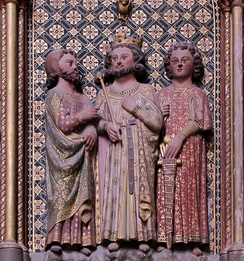 Charles in a 14th-century sandstone relief, flanked by a squire and a knight.