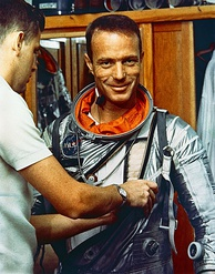 Carpenter is assisted into his pressure suit in the crew quarters of Hanger S at Cape Canaveral Air Force Station on the morning of the flight of Mercury Atlas 7.