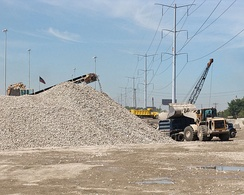 Recycled crushed concrete, to be reused as granular fill, is loaded into a semi-dump truck