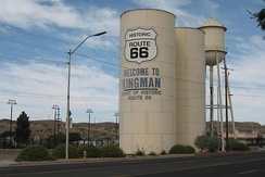 "A ""Welcome to Kingman"" sign on a water tower, marking its connection with Route 66"