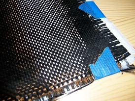 A cloth of woven carbon fiber filaments, a common element in composite materials