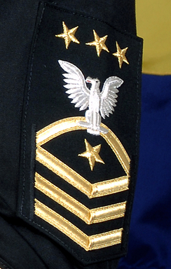 The rating badge of the Master Chief Petty Officer of the U.S. Navy, worn on a service dress blue uniform's sleeve.