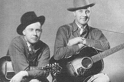 Bill and Charlie Monroe (1936). Bill Monroe (1911–1996) and The Blue Grass Boys created the bluegrass by the end of World War II.