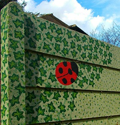 Mural of ladybird in Robin Hood Lane on the side wall of the path leading to St Nicholas Church