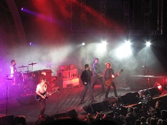 Powderfinger are on stage, with Coghill at left on drums, then Middleton on guitar, Fanning mid-stage singing into a microphone, Collins on his bass guitar and Haug at extreme right.