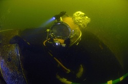 Navy Reserve Navy Diver Seaman Jesse Kole, assigned to Naval Experimental Diving Unit, does an inspection dive of the interior of the wreck of the former Russian submarine Juliett 484.