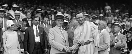 President Calvin Coolidge (left) and Washington Senators pitcher Walter Johnson (right) shake hands.