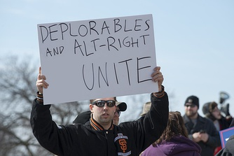 An alt-right supporter at the March 4 Trump rally in Saint Paul, Minnesota; due to copyright issues, a depiction of Pepe the Frog on the man's sign has been digitally removed[notes 1]