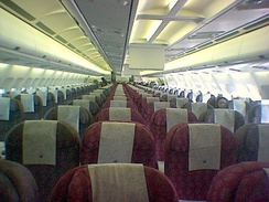 Interior of a Qatar Airways Airbus. Video systems (the vertical white panels) are visible above the very centre seats of the aircraft
