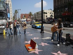 Several stars on the Walk of Fame at 6801 Hollywood Boulevard, with Street performers and passersby