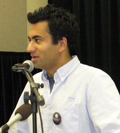 A man giving a speech. He wears a white blouse with a dark label pin. In front of him, there are two microphones.