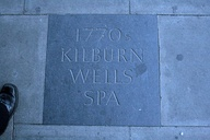 Paving stones in Kilburn, commemorating the route of Watling Street on High Road (left) and commemorating the former Wells on the corner of Belsize Road and the High Road (right)
