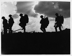 Image taken during the Battle of Broodseinde, showing a group of British soldiers of the 8th (Service) Battalion, East Yorkshire Regiment, part of the 62nd Brigade of the 21st Division, moving up to the front, silhouetted against the skyline. Photo taken by Ernest Brooks.