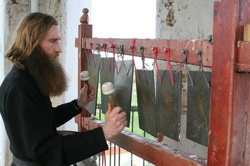 A Russian monk playing a semantron