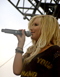 "Tisdale, on a stage, sings into a microphone, holding it with her right hand. She is wearing a black blouse with the words ""Your"" and ""Band"" printed on it in yellow and few bracelets on her right arm."