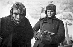 A Red Army soldier marches a German soldier into captivity.