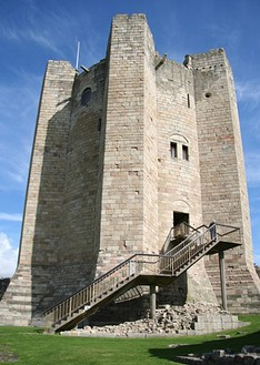 A circular castle tower with enormous jutting buttresses. There are few windows and entrance is on an upper floor, is reached by a modern staircase.