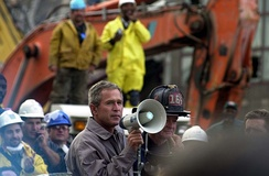 President Bush, standing with firefighter Bob Beckwith, addressing rescue workers at Ground Zero in New York, September 14, 2001
