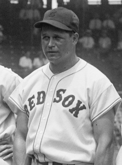 "A man is pictured from his belt up looking to the left of the camera. His button-down baseball jersey says ""RED SOX"" across it and he is wearing a baseball hat with a ""B""."