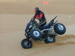 Quad bike two-wheel trick-riding on sand dune.