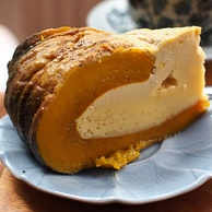 Slice of yellowish pumpkin custard with brown shell